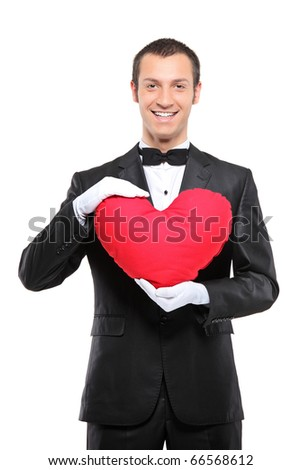 A happy man holding a red heart-shaped pillow isolated against white background