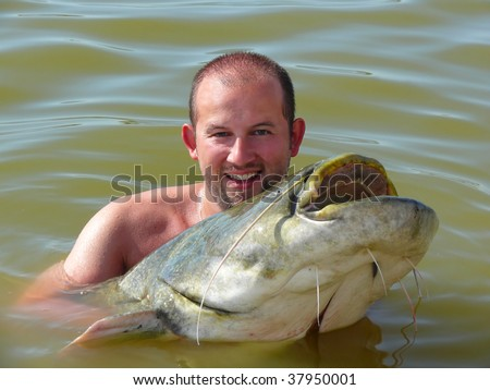 A happy man with a catfish he just caught - stock photo