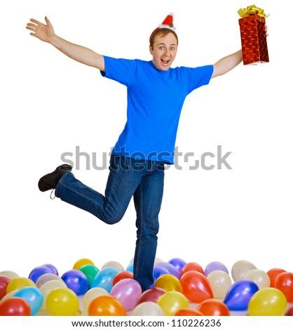 A happy man with a Christmas gift dancing among balls - stock photo