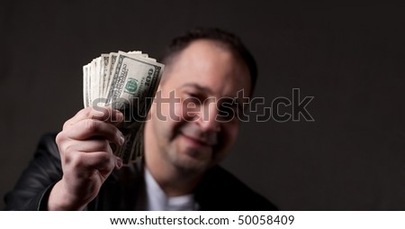 A happy middle aged man holding a handful of money with copyspace. - stock photo