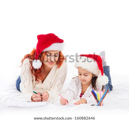 A happy mother and daughter in Christmas hats drawing with markers - stock photo