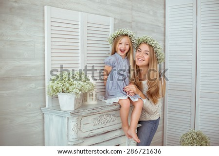 A happy mother and her daughter are excited. They are smiling and looking straight.  - stock photo