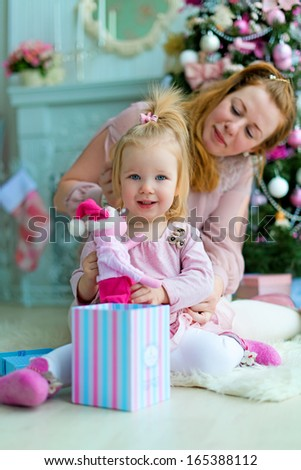A happy mother and her little daughter sitting on the floor against the Christmas Tree and opening the Christmas presents - stock photo