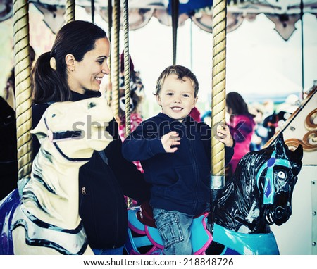 A happy mother and son are riding on a merry-go-round carousel together, smiling and having fun at a fair or amusement park.  The boy is waving.  Filtered for a retro, vintage look.  - stock photo