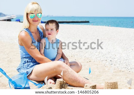 A happy  mother and young child boy son having fun in the sand together