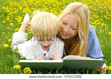 a happy mother is laying in the Dandelion flowers outside with her young child, reading him a story from a book.