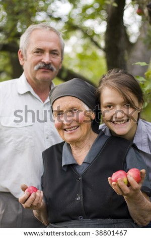 A happy multi-generation family in the garden with apples. - stock photo