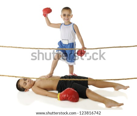 A happy preschool boxer with a missing tooth and black eye raising his fist in victory as his elementary-aged brother lies beaten on the ground.  On a white background. - stock photo