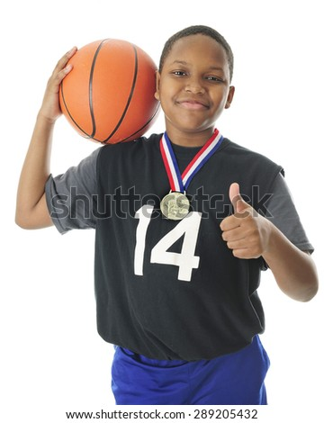 A happy preteen athlete supporting his basketball on his shoulder, a thumbs up with the other hand and a red, white and blue winning ribbon and metal around his neck.  On a white background.   - stock photo