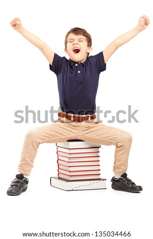 A happy schoolboy raised his hands gesturing happiness, seated on a pile of books against white background - stock photo