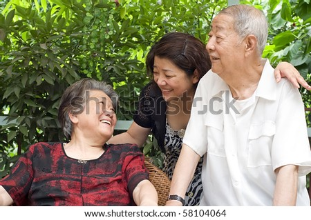 a happy senior couple and their daughter - stock photo