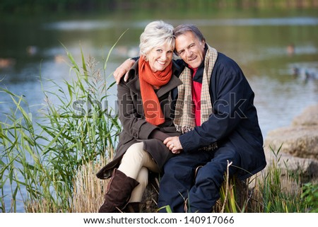 A happy senior couple posing by the lake