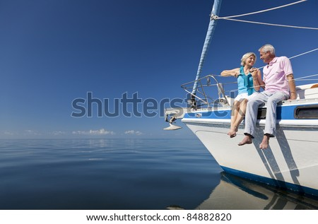 A happy senior couple sitting on the front of a sail boat on a calm blue sea - stock photo