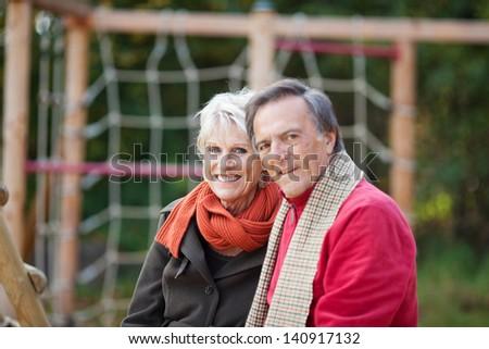A happy senior couple sitting on the playground - stock photo