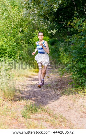 A happy senior woman is running in the forest during a warm summer day