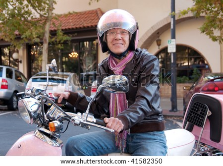 a happy sixty year old woman on her scooter - stock photo