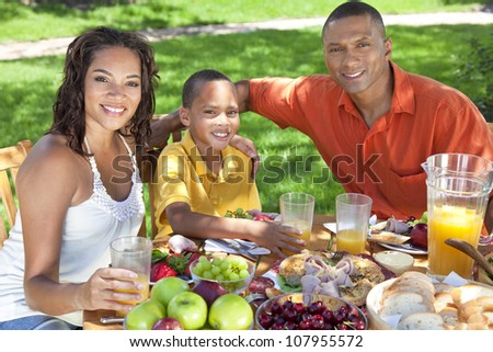 A happy, smiling African American family, mother father & son eating healthy food at a table outside, the father is serving a orange juice to the boy. - stock photo