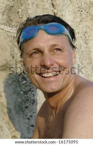A happy smiling forties man wearing swimming goggles.