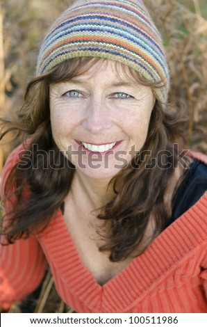 A happy smiling mature woman with freckles and wearing a colorful beanie hat.
