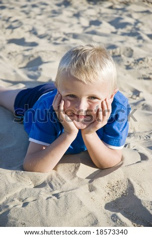A happy smiling 7 year old child laying on a sandy beach - stock photo