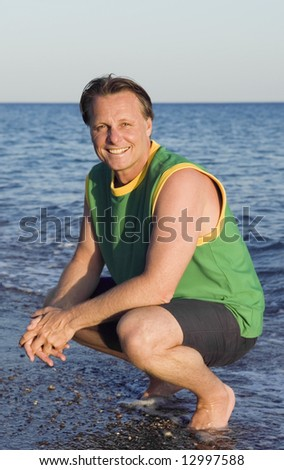 a happy smiling 44 year old man relaxing on beach holiday.