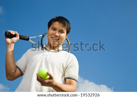 A happy sporty asian male playing tennis - stock photo