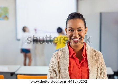 A happy teacher posing for the camera in classroom