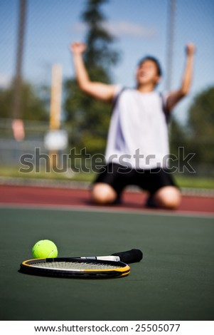 A happy tennis player in joy after winning - stock photo