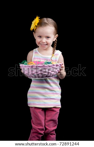 A happy toddler looks excited to show the viewer her basket full of eggs. - stock photo