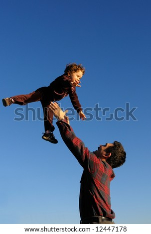 A happy two year old girl tossed into the blue sky by her father - vertical (portrait) orientation. - stock photo