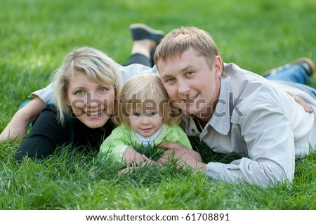 A happy united family are lying in the park