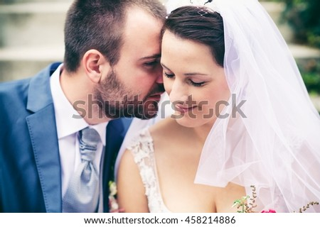 A happy wedding couple. The groom whispers something to the bride's ear and she is smiling. A happy moment in human life. - stock photo