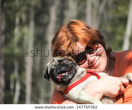A happy woman and her pug picture. - stock photo