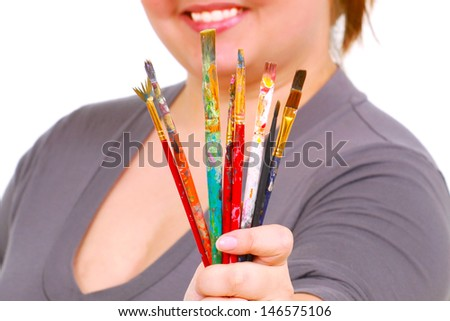 A happy woman holds dirty art brushes - stock photo