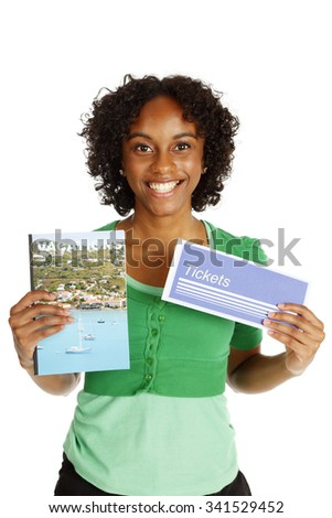 A happy woman holds up a generic travel brochure and generic ticket envelope.