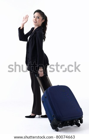 A happy woman pulling her luggage and waving her hand to good bye her family - stock photo