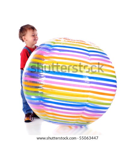 A happy 2-year-old ready to push a giant beach ball.  Isolated on white. - stock photo