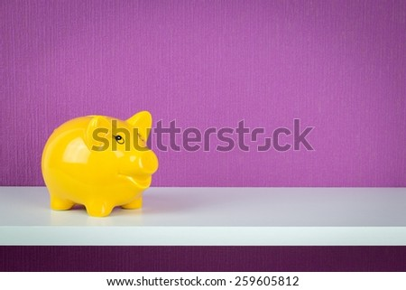 A happy yellow piggy bank on a shelf with copy space background - stock photo