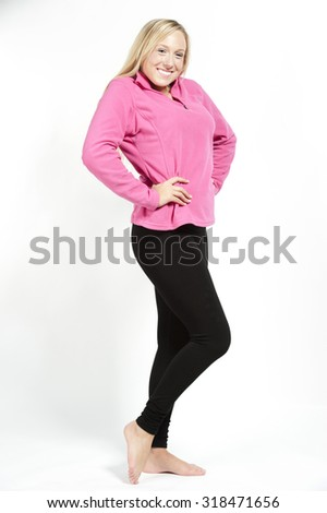 A happy young attractive female model wearing a pink sweatshirt with black pants on a white background. - stock photo