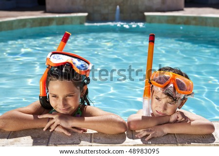 A happy young boy and girl relaxing on the side of a swimming pool wearing orange goggles and snorkel - stock photo
