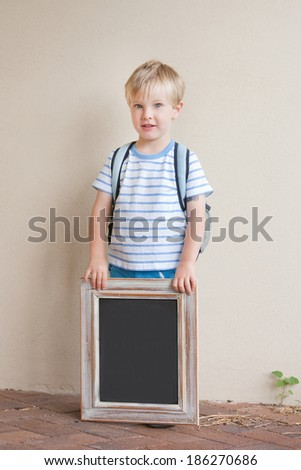 A happy young boy with a backpack holding a chalkboard against a white background.    - stock photo