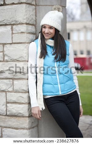A happy young brunette girl wearing a white hand and a blue jacket on a sunny day.