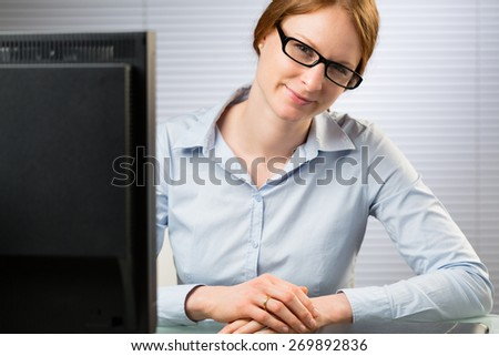 A happy young businesswoman sits behind a desktop computer and smiles at the camera.