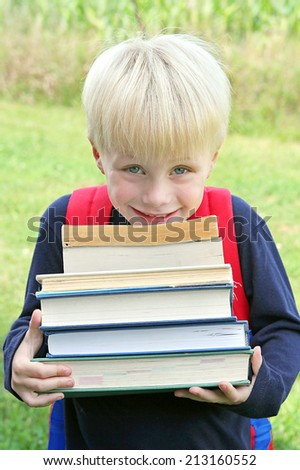 A happy young child is carrying a big stack of heavy school books. - stock photo