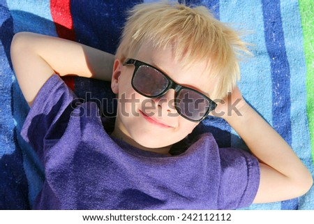 A happy young child is relaxing with his hands behind his head on a rainbow striped beach towel, while wearing sunglasses on summer vacation. - stock photo