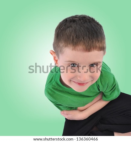 A happy young child is sitting down looking up on an isolated green background with copyspace. The boy is thinking with his hands crossed. - stock photo