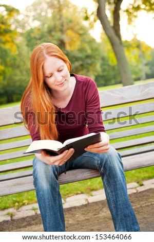 A happy young Christian woman reading a Bible in a park. - stock photo