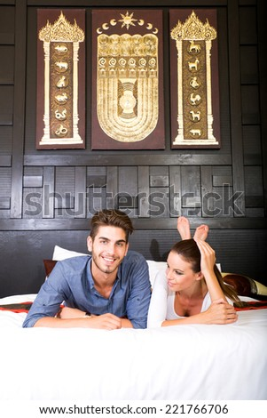 A happy young couple on their vacations lying on the bed in an asian style hotel room. - stock photo