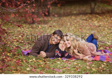 A happy young family lay on a plaid in a park in autumn - stock photo