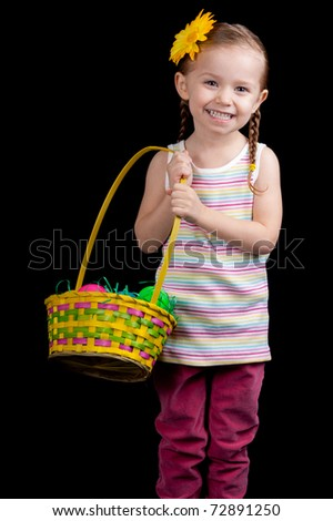 A happy young girl holding her easter basket.  She is on the hunt for more eggs. - stock photo